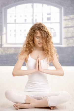 Young attractive woman practicing yoga, meditating in prayer pose, eyes closed, sitting on floor. photo