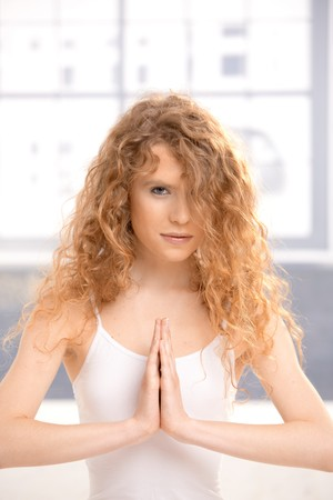 Pretty girl practicing yoga, meditating in prayer pose sitting on floor. Stock Photo - 8083468