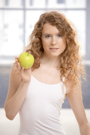 Pretty, healthy girl after workout, holding apple in her hand. Stock Photo - 8083467