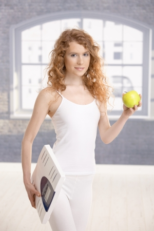 Attractive girl holding apple and scale in hands, living healthy. photo