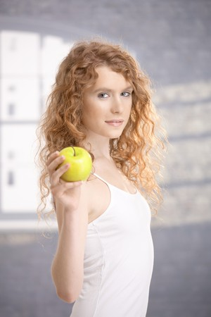 Pretty, healthy girl after workout, holding apple in her hand. photo