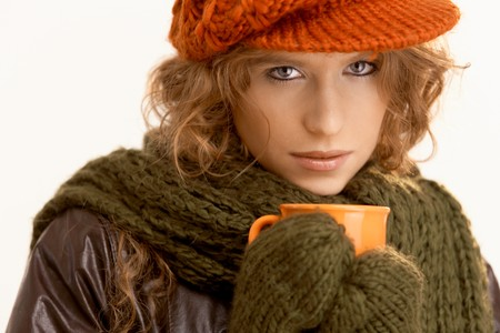 Pretty young woman dressed up warm, drinking hot tea, freezing. photo