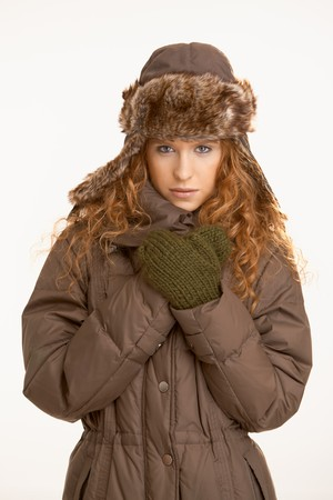 Attractive girl dressed up in coat, scarf, gloves and fur- hat. photo