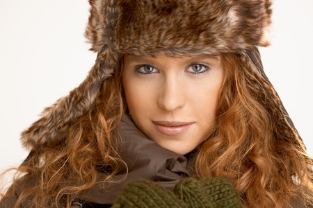 Attractive girl dressed up in coat, scarf and fur- hat. photo