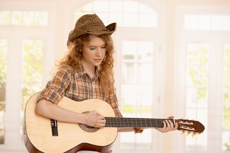 Attractive girl playing on guitar, dressed in country style. photo