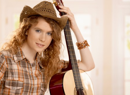 Attractive girl leaning on guitar, dressed in country style. photo