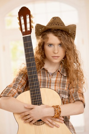 Attractive girl embracing her guitar, dressed in country style. Stock Photo - 8083496