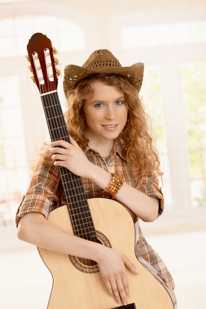 Pretty young woman hugging her guitar, dressed in country style. photo