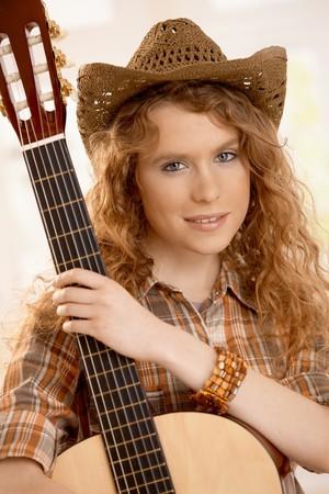 western european: Attractive female hugging her guitar, dressed in western style.