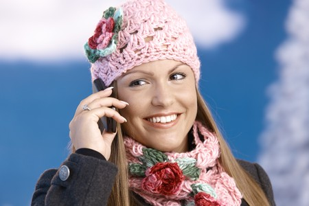 Attractive young woman dressed up warm in coat, cap and scarf, smiling front of winter landscape using mobile phone . photo