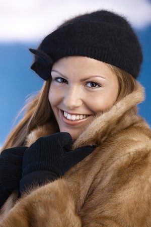 Elegant young woman dressed up warm in fur coat, cap and gloves, enjoying wintertime, smiling. photo