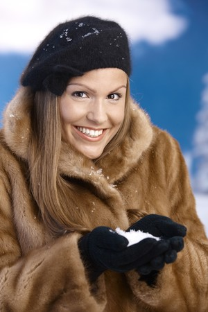 Elegant young woman dressed up warm in fur coat, cap and gloves, holding snow in hands, smiling. photo
