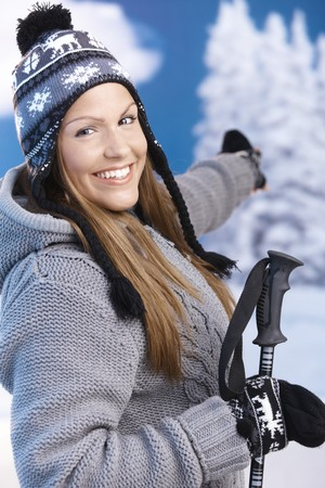 Attractive young female dressed up warm for skiing wearing cap and gloves smiling and pointing to winter landscape . photo