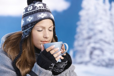 warm drink: Pretty young girl dressed up warm for skiing wearing cap and gloves drinking hot drink eyes closed front of winter landscape . Stock Photo