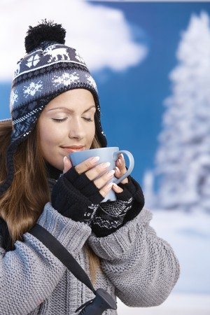 Pretty young girl dressed up warm for skiing wearing cap and gloves drinking hot tea eyes closed front of winter landscape . photo
