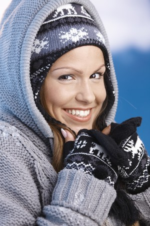 Attractive young female dressed up warm for skiing wearing cap and gloves, resting, smiling. photo