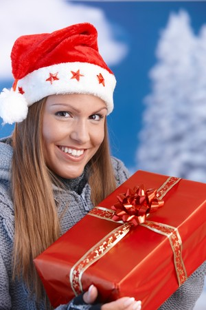 Happy young woman in santa hat holding christmas present, looking at camera, smiling. Stock Photo - 8121337