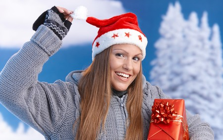Happy young woman in santa hat holding christmas present, looking at camera, smiling. photo