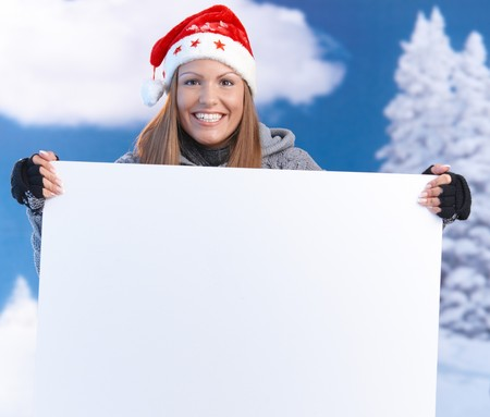 Attractive young woman in santa hat holding huge blank letter front of herself, smiling. photo