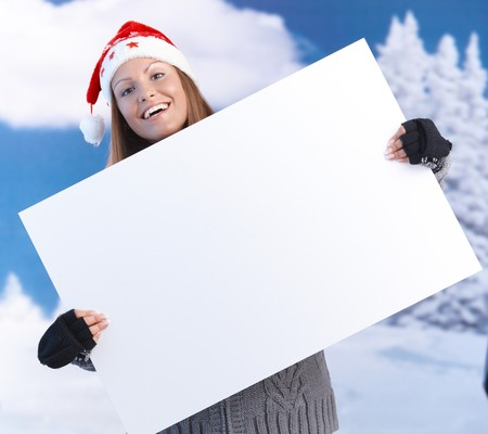 Attractive young woman in santa hat holding huge blank letter front of herself, smiling. Stock Photo - 8121228