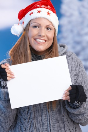 Attractive young woman in santa hat holding blank letter front of herself, smiling front of snowy landscape. photo
