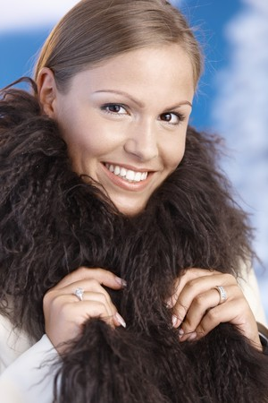 Portrait of elegant young woman enjoying winter front of snowy landscape, wearing fur scarf, smiling. photo