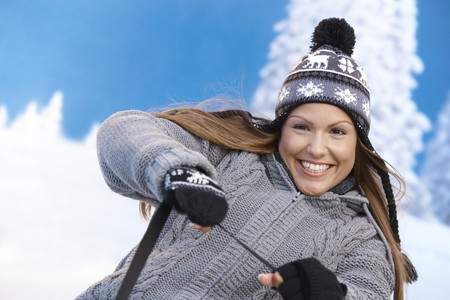 Young female having winter fun, being drawn by sleigh, smiling. photo