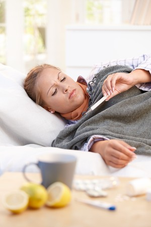 fiebre: J�venes mujeres en casa con la gripe, sensaci�n de malestar, tomando su temperatura en la cama.