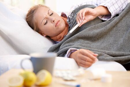 cold and flu: Young female at home having flu, feeling bad, taking her temperature in bed.