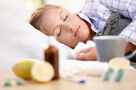 cold and flu: Young female in bed at home caught cold, feeling bad, taking medicines and vitamins, sleeping.
