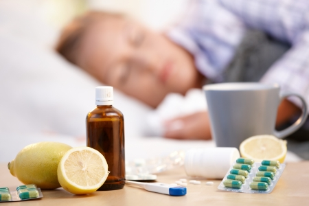 nightdress: Vitamins, medicines and hot tea in front, woman caught cold sleeping in background. Stock Photo