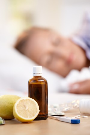 nighty: Vitamins, medicines and lemons in front, woman caught cold sleeping in background. Stock Photo