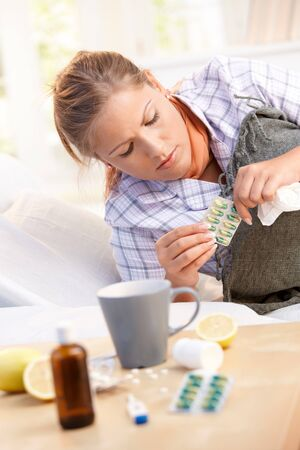 Woman having flu curing herself with witamins, medicines, tea, laying in bed. Stock Photo - 8121300