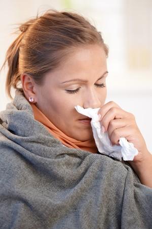 chaud froid: Jeune femme prise froid, sentiment mauvaises, soufflant son nez, envelopp� dans une couverture.