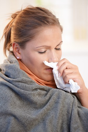 weary: Young woman caught cold, feeling bad, blowing her nose, wrapped up in blanket. Stock Photo