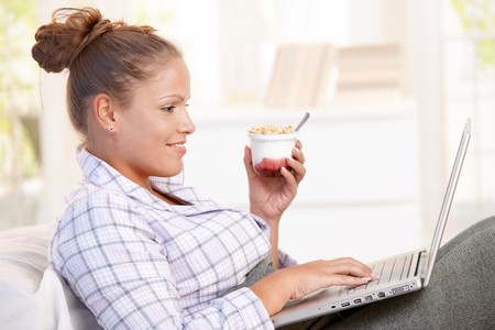 Young woman browsing Internet in bed, using laptop, smiling, eating yoghurt. Stock Photo - 8121306