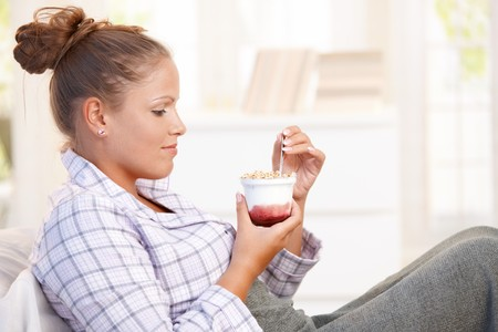 Attractive young woman dieting, eating yoghurt in bed. Stock Photo - 8121327