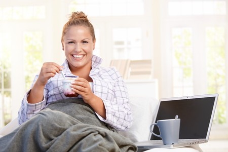Young female having breakfast at home, dieting, eating yoghurt in bed, using laptop. photo