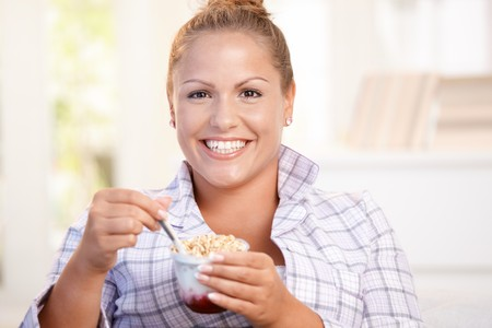 Young female having breakfast at home, dieting, eating yoghurt. Stock Photo - 8121258