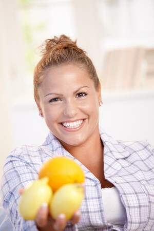 Portrait of young woman holding lemons in her hand smiling, living healthy. Stock Photo - 8121257