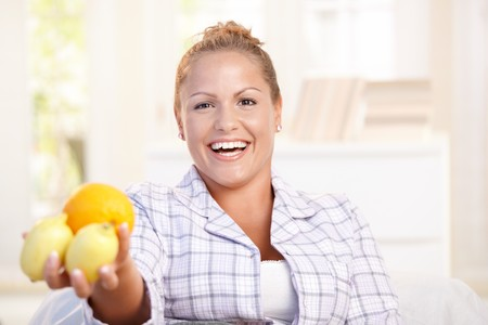 nighty: Portrait of young woman holding lemons in her hand smiling, living healthy.
