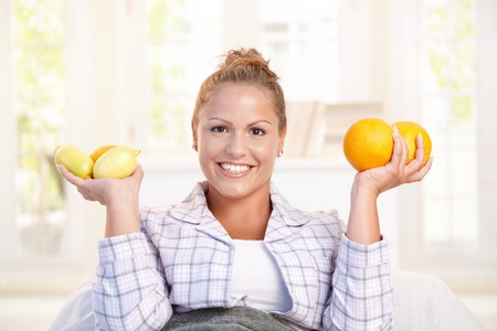 nighty: Portrait of young woman holding lemons and grapefruits in her hand smiling, living healthy. Stock Photo