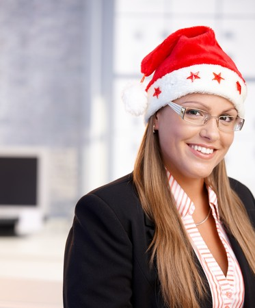 Portrait of young woman wearing santa claus hat in office, smiling. photo