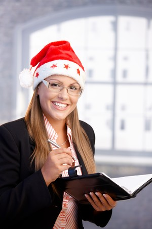 Young secretary wearing santa hat, holding appointment book, smiling in office. Stock Photo - 8121293