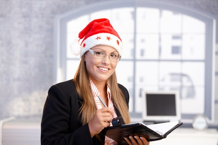 Young secretary wearing santa hat, holding appointment book, smiling in office. Stock Photo - 8121266