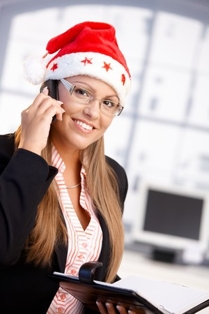 Pretty female wearing santa hat, holding organiser, using mobile, smiling in office. photo