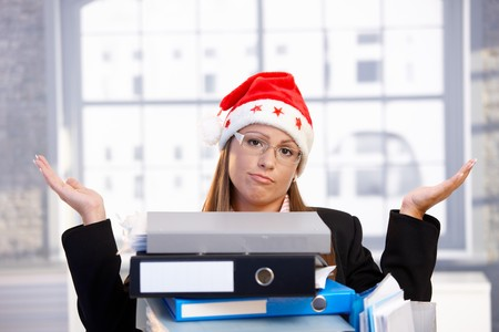 Young woman in santa hat sitting in office behind folders, having trouble. photo