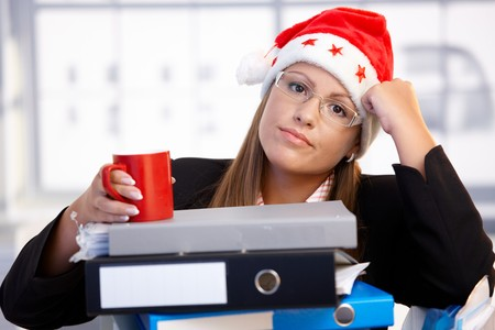 Young woman in santa hat sitting in office leaning on folders, exhausted, taking a break. photo