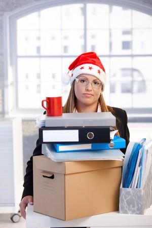 Young woman in santa hat sitting in office dejected behind folders, having trouble, taking a break. photo