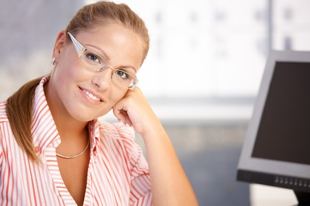 wearing glasses: Portrait of young woman sitting at desk, working with computer, smiling.
